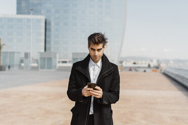 Portrait of businessman holding cell phone in the city - AFVF02907