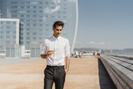 Portrait of businessman with takeaway coffee in the city - AFVF02916