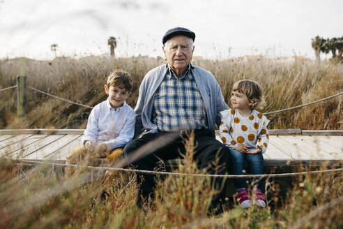 Portrait of grandfather sitting with his grandchildren side by side on boardwalk - JRFF03183