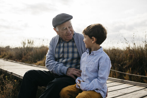 Happy grandfather sitting with his grandson on boardwalk looking at each other - JRFF03186