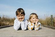Portrait of boy and his little sister lying side by side on boardwalk - JRFF03192