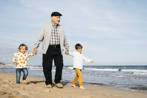 Grandfather strolling with his grandchildren hand in hand on the beach - JRFF03207