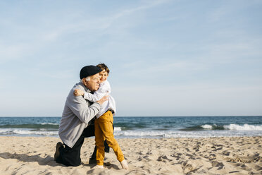 Grandfather and grandson hugging on the beach - JRFF03216