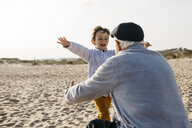 Portrait of little boy running into his grandfather's arms on the beach - JRFF03219