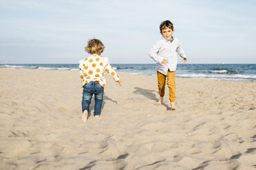 Boy and his little sister playing on the beach - JRFF03225