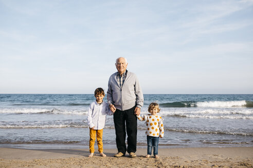 Portrait of happy grandfather standing hand in hand on the beach with his grandchildren - JRFF03231
