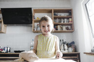 Portrait of smiling little girl rolling out dough in the kitchen - KMKF00903