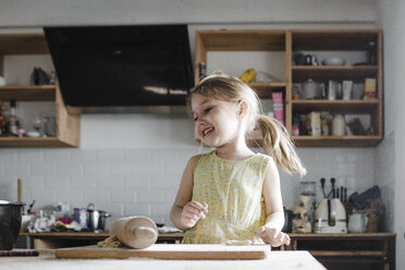 Happy little girl rolling out dough in the kitchen - KMKF00906