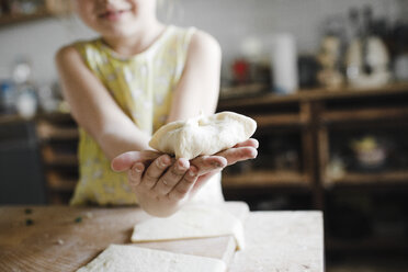 Girl's hands holding homemade stuffed pastry, close-up - KMKF00909