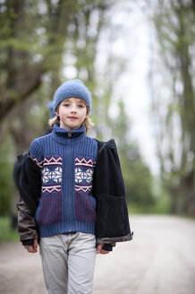 Portrait of young boy wearing blue hat and sweater in a park - EYAF00190