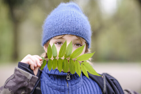 Germany, Dortmund, portrait young boy in blue hat and sweater looking through green leaf - EYAF00193