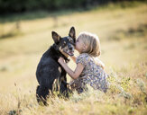 Caucasian girl sitting in field kissing dog - BLEF02146