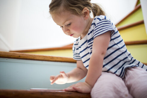 Caucasian girl using digital tablet on staircase - BLEF02176