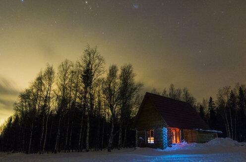 Light glowing in remote cabin in winter - BLEF02218