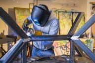 Caucasian man welding metal sculpture - BLEF02248