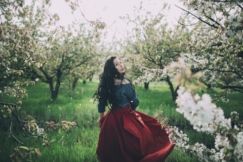 Caucasian woman walking near flowering trees - BLEF02266
