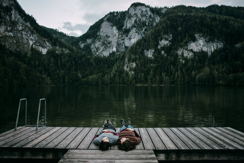 Caucasian couple laying on dock near scenic view of mountain - BLEF02272