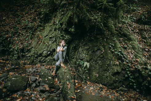 Caucasian woman sitting in forest holding branch - BLEF02275