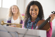 Smiling girls posing with violin and trumpet - BLEF02303