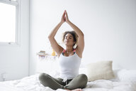 Mixed Race woman sitting on bed meditating - BLEF02333
