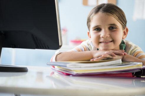 Smiling Caucasian girl leaning on notebooks at desk - BLEF02381