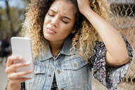 Unhappy Mixed Race woman texting on cell phone - BLEF02414