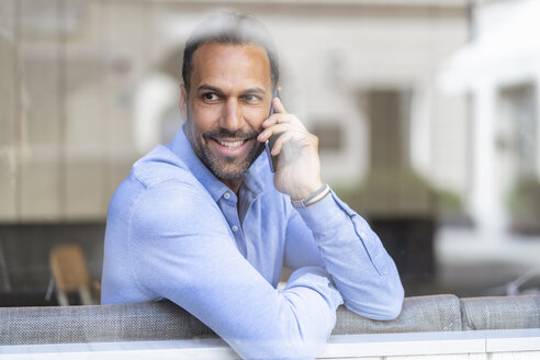 Smiling businessman on cell phone behind windowpane - DIGF06945