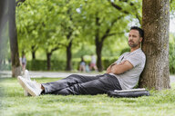 Man leaning against a tree in park having a nap - DIGF07002