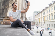 Smiling man taking a selfie in the city - DIGF07011