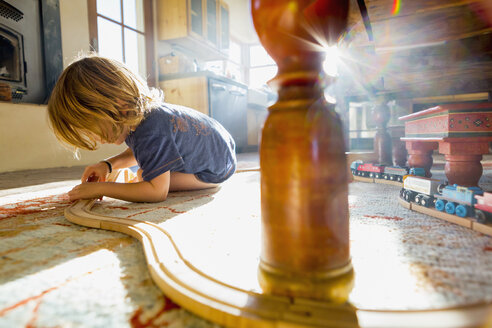 Caucasian boy playing with toy race track on floor - BLEF02530