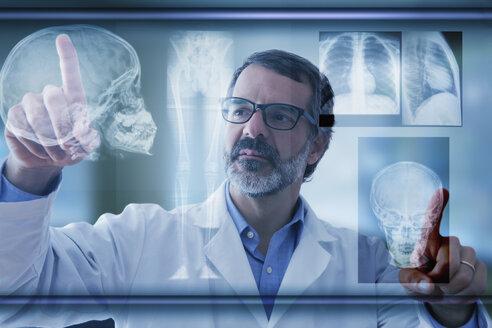 Hispanic doctor examining x-rays on virtual screen - BLEF02575