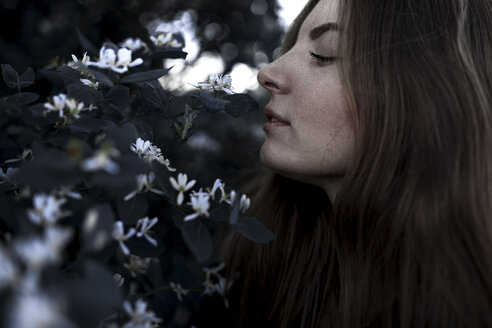 Caucasian woman smelling flowers outdoors - BLEF02605