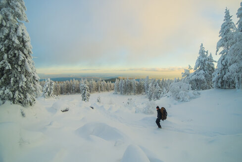 Caucasian man hiking in snowy forest at sunset - BLEF02674