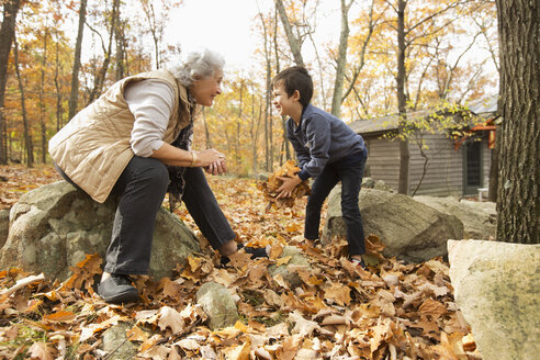 Grandmother and grandson playing with autumn leaves - BLEF02707