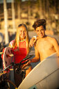 Teenage boy and girl posing with surfboards and bicycles - BLEF02737