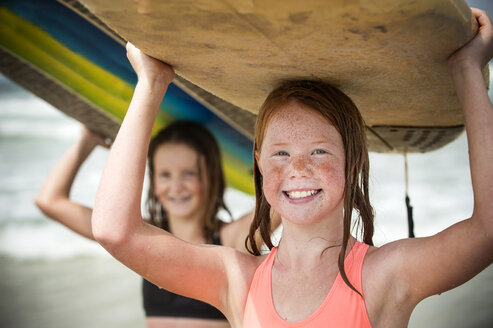 Portrait of smiling girls balancing surfboards on top of heads - BLEF02761