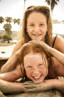 Portrait of smiling girls laying on beach covered with sand - BLEF02764