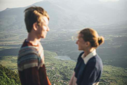 Caucasian couple standing on mountain over valley - BLEF02836