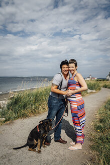 Portrait of pregnant lesbian couple with dog hugging at waterfront - BLEF02842