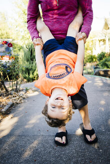 Caucasian mother holding son upside-down - BLEF02860