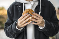 Hands of young woman with painted nails holding a hamburger, close-up - ACPF00505