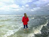 Belgium, Flanders, North Sea, woman standing barefoot in ocean waves, relaxing - GWF06070