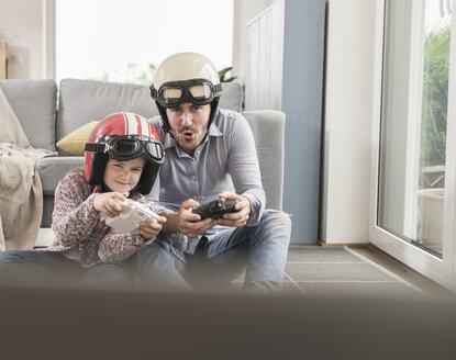 Young man and little girl wearing biker helmets, playing racing game with gaming consoles - UUF17341