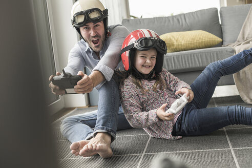 Young man and little girl wearing biker helmets, playing racing game with gaming consoles - UUF17344