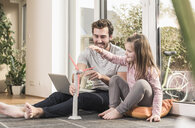 Young man and little girl playing with model of a wind turbine - UUF17362