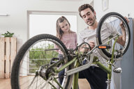 Young man and little girl repairing bicycle together - UUF17365
