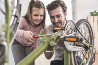 Young man and little girl repairing bicycle together - UUF17371
