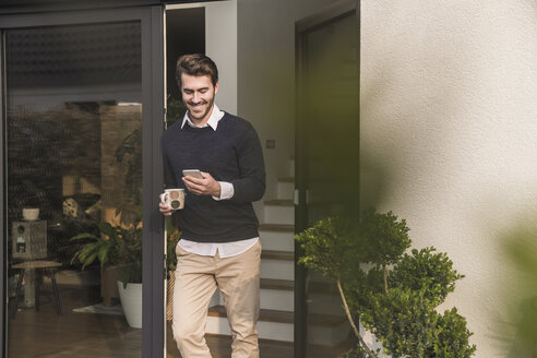 Young man leaning in door of his house, holding cup of coffee, using smartphone - UUF17374