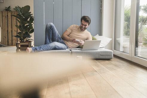 Young man sitting on mattress, using laptop, taking notes - UUF17395