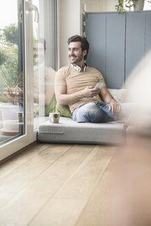 Young man sitting on mattress, using smartphone with headphones around neck - UUF17401